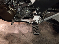 Lowered wide foot peg on Husqvarna FE501s motorcycle, Trakker stainless steel tread with black anodized base