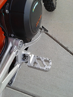 Wide Lowered Foot Pegs on KTM 690 Enduro Motorcycle, Silver with Trakker Tread